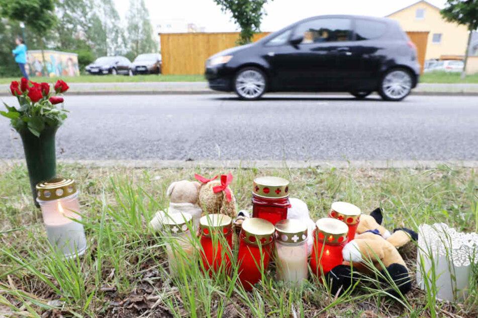 Blumen, Kerzen und Plüschtiere stehen an der Stelle am Straßenrand in Rostock, wo der tote Säugling gefunden wurde.