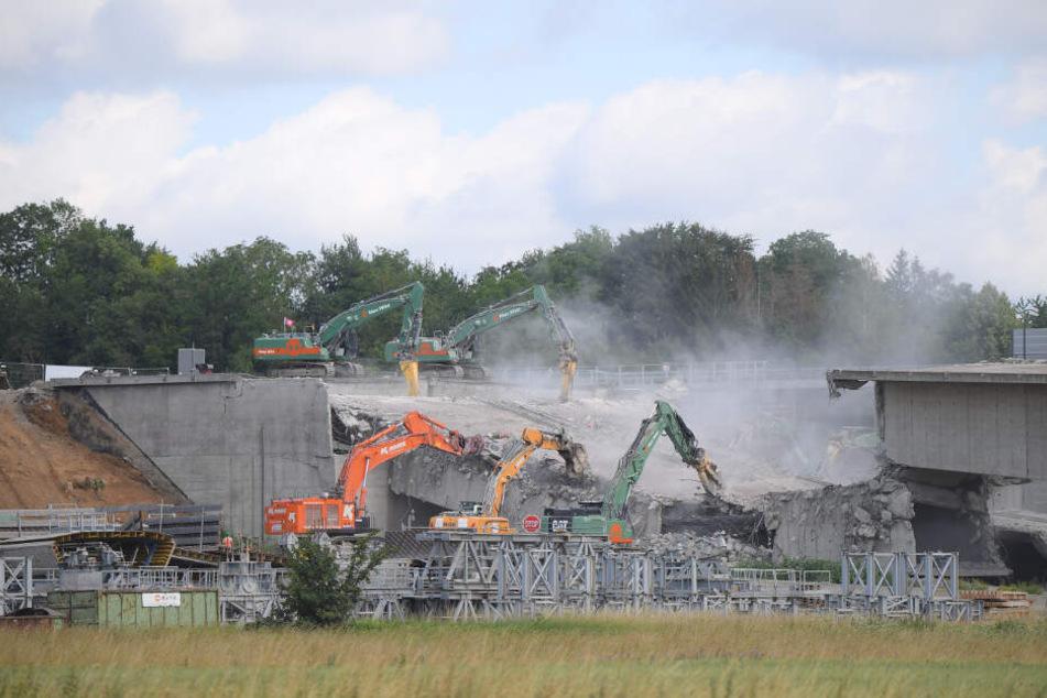 Unmittelbar nach der Sprengung wird die Brücke von Baggern abgebrochen.