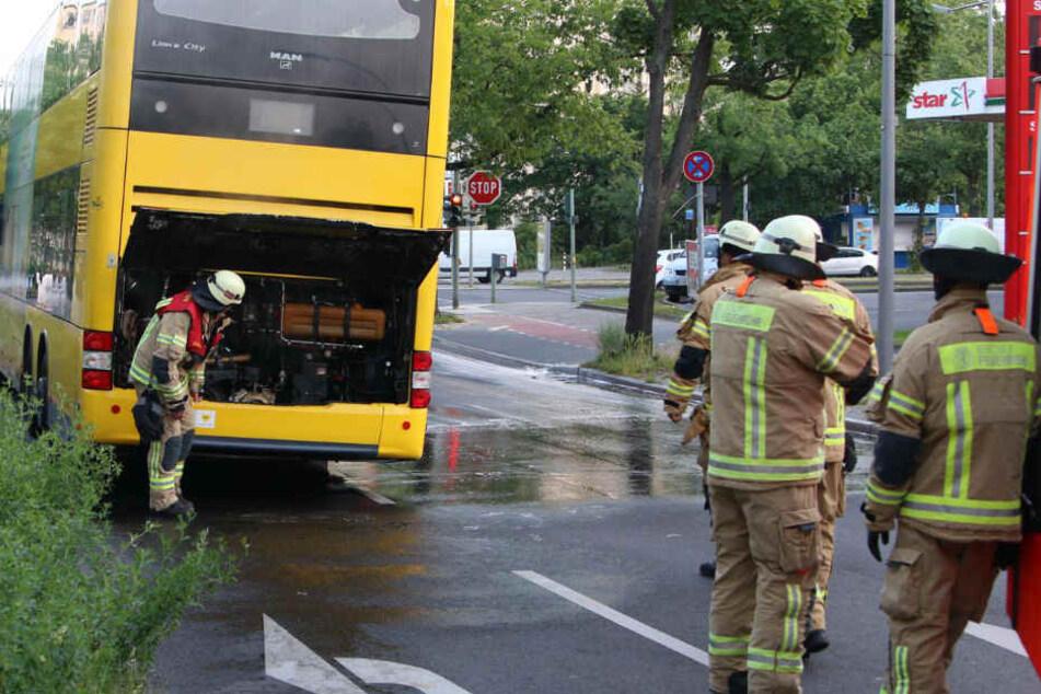 Feuerwehrmänner checken den Heckbereich des Doppeldeckers.
