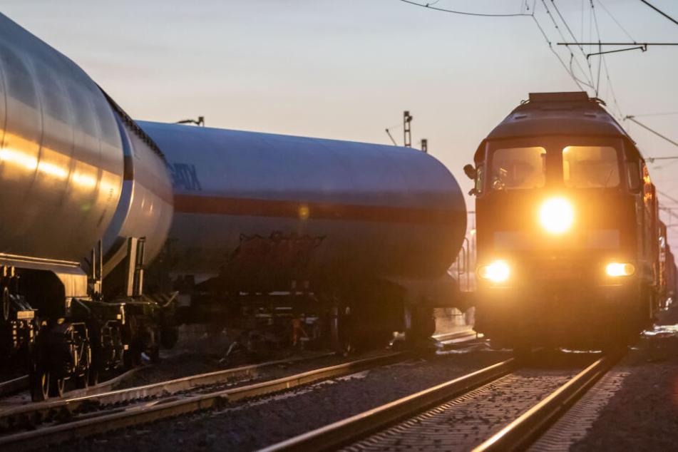 Ein Zug mit einem Bergekran fährt an einem Entgleisten Waggon vorbei.