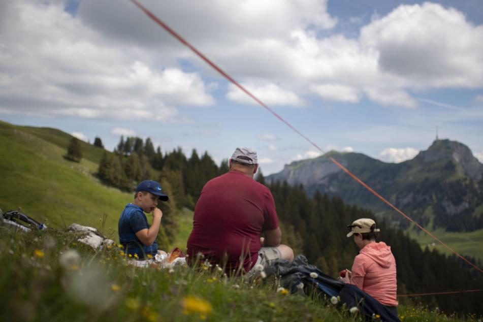 Schweiz, Brülisau: Eine Familie picknickt auf der Alp Sigel mit Blick auf den Hohen Kasten.