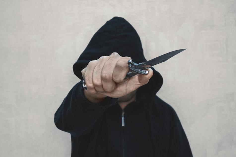 Einer der beiden Täter bedrohte einen Kunden mit einem Messer am Hals (Symbolbild).