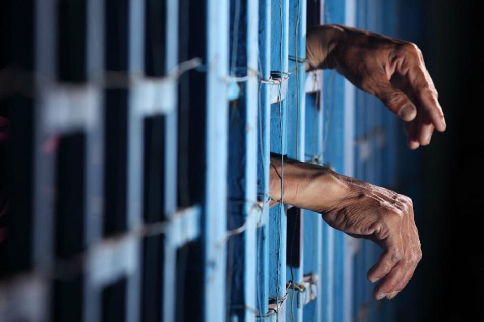 Hände eines Gefangenen hängen aus einer Zelle. (Symbolbild)
