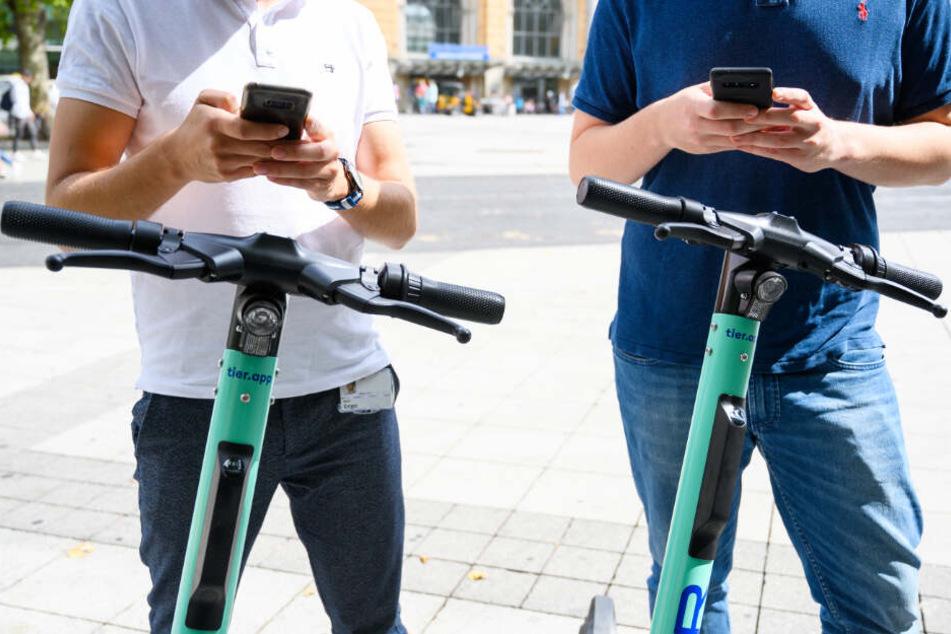 Zwei Männer leihen sich per Handy-App E-Scooter aus. (Symbolbild)