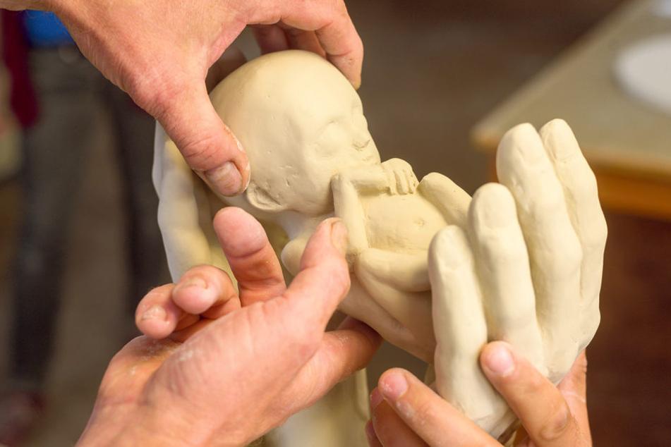 So wird der Preis aussehen: Zwei Hände halten schützend ein Neugeborenes.