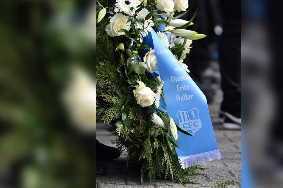 Ein Trauergesteck mit einer himmelblauen Schleife und dem CFC-Logo.