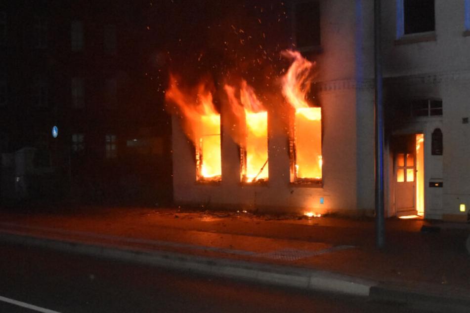 Flammen schlagen aus den Fenstern des Mehrfamilienhauses.
