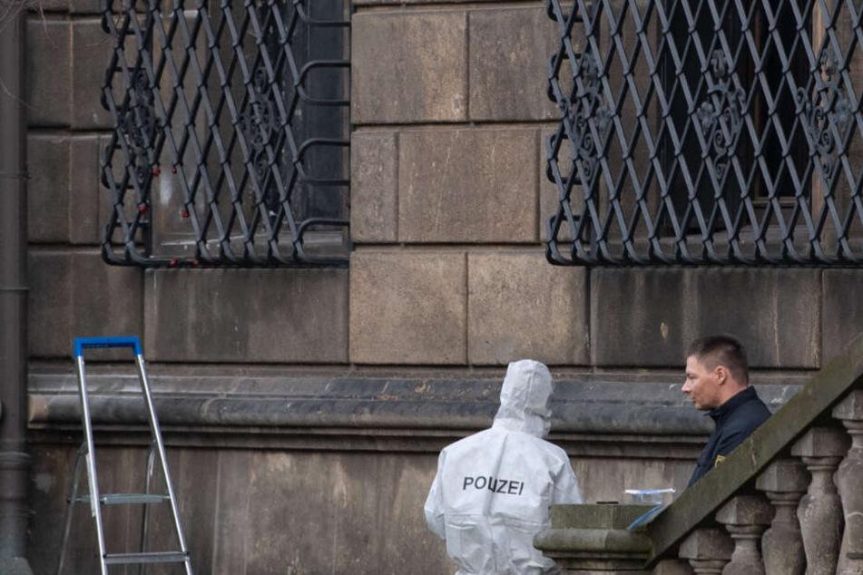Einsatzkräfte der Polizei neben dem durchtrennten Gitterfenster.
