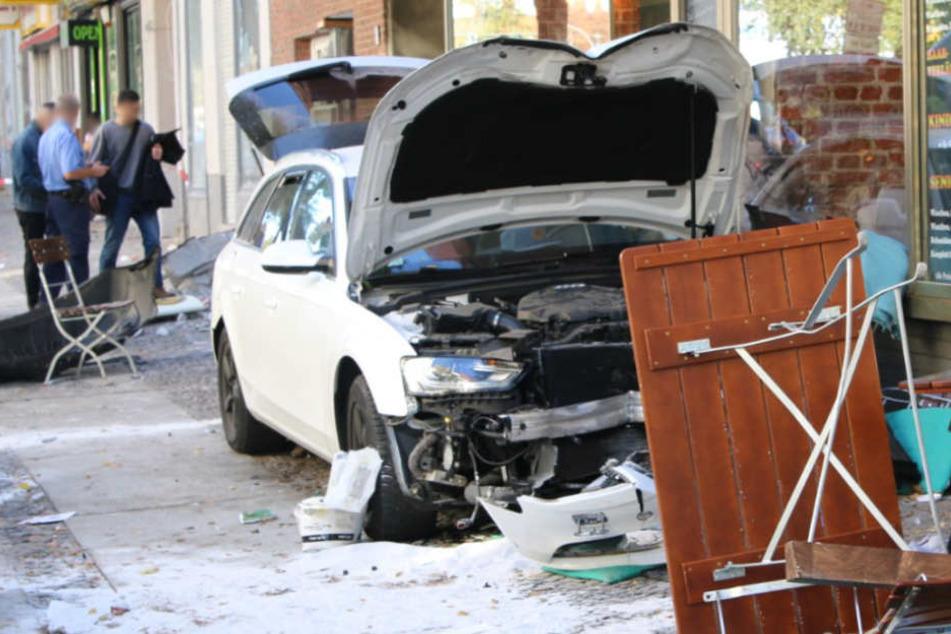 Der stark beschädigte weiße Audi vor dem Café.