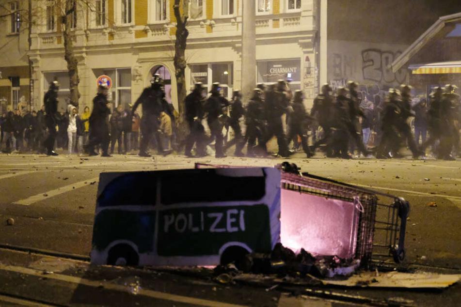 Ein Einkaufswagen mit einem gebastelten Polizei-Auto aus Pappe - die Randalierer sollen den brennenden Wagen in eine Gruppe Polizisten geschoben haben.