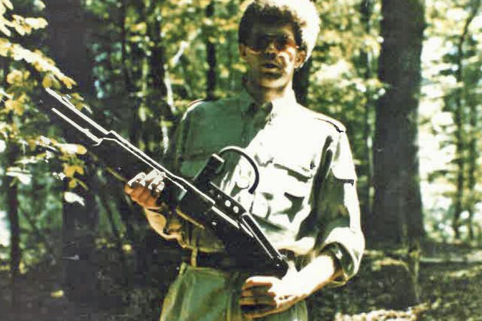 Das von der belgischen Polizei veröffentlichte Foto zeigt einen Mann mit Sonnenbrille, der im Wald steht, militärähnliche Kleidung trägt und eine Waffe hält.