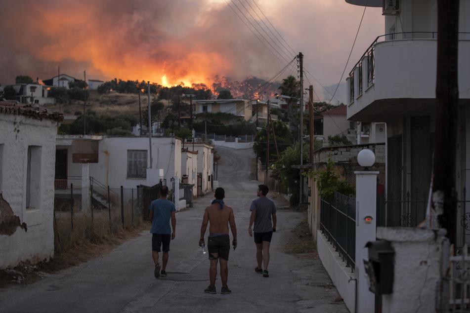 Drei Männer beobachten ein Feuer in der Nähe des Dorfes Galataki.