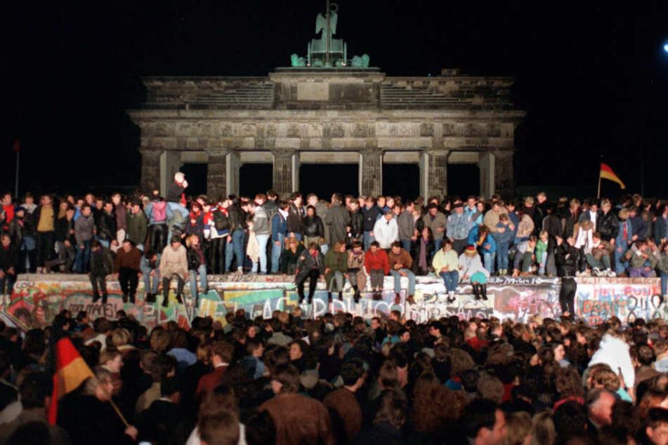 10. November 1989: Jubelnde Menschen auf der Berliner Mauer am Brandenburger Tor.