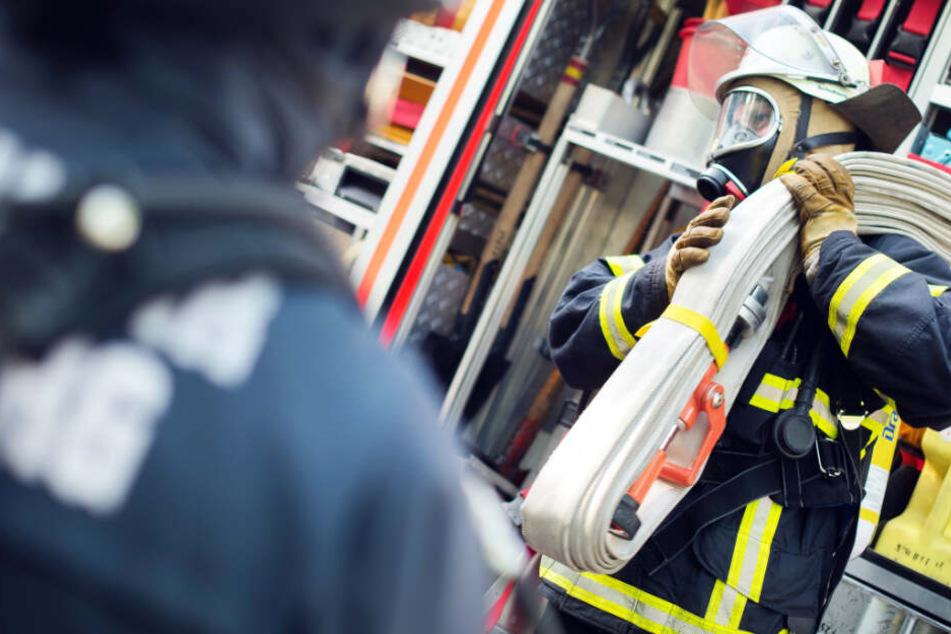 Mit Atemschutz ausgerüstete Feuerwehrkräfte retteten eine Person aus der brennenden Wohnung (Symbolbild).