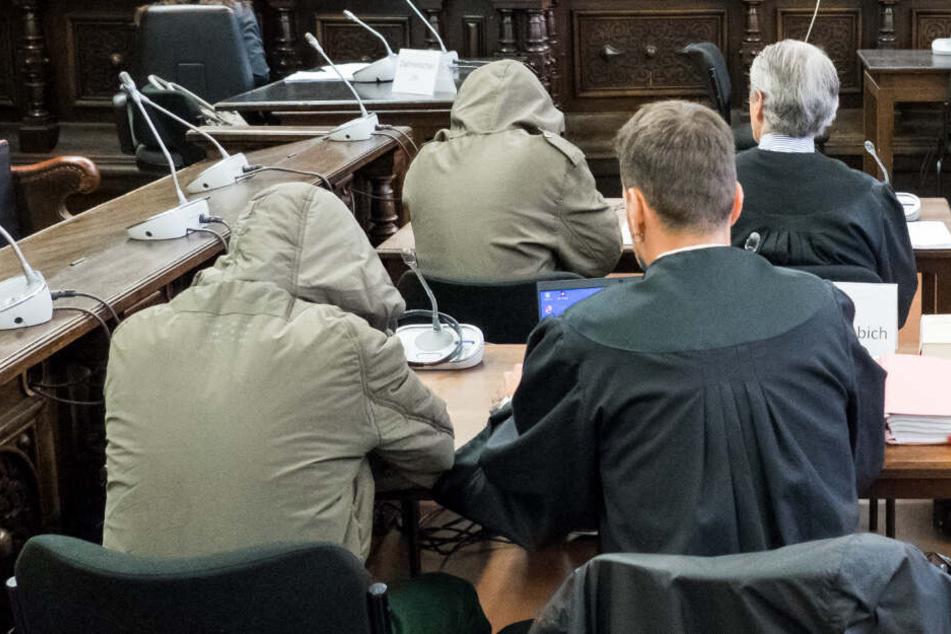 Die Angeklagten sitzen neben ihren Verteidigern im Gerichtssaal