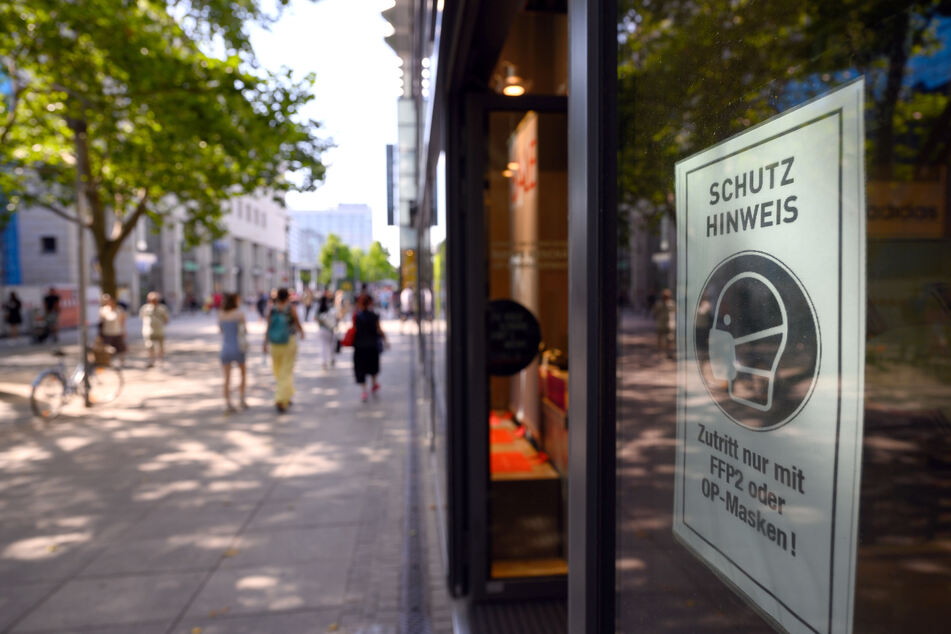 Ein Schild mit dem Hinweis auf die Maskenpflicht klebt am Schaufenster eines Modegeschäfts auf der Einkaufsmeile Prager Straße. Bleibt die Inzidenz weiter über 10, könnten bisherige Lockerungen zurückgenommen werden.