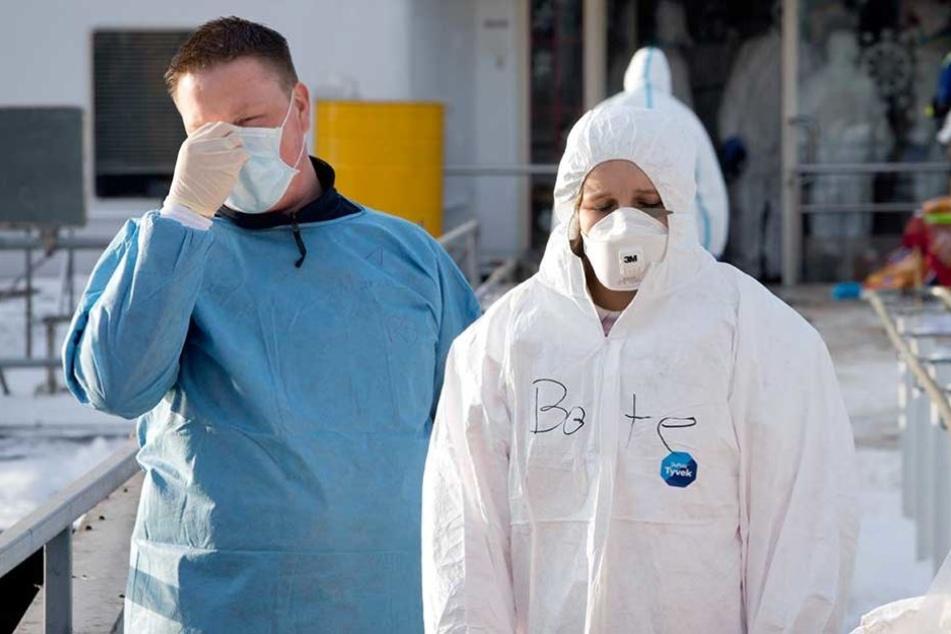 Der Norovirus wird über Tröpfchen übertragen und ist deshalb sehr ansteckend. Hilfskräfte tragen deshalb Schutzausrüstung, wenn sie mit Erkrankten in Kontakt kommen.
