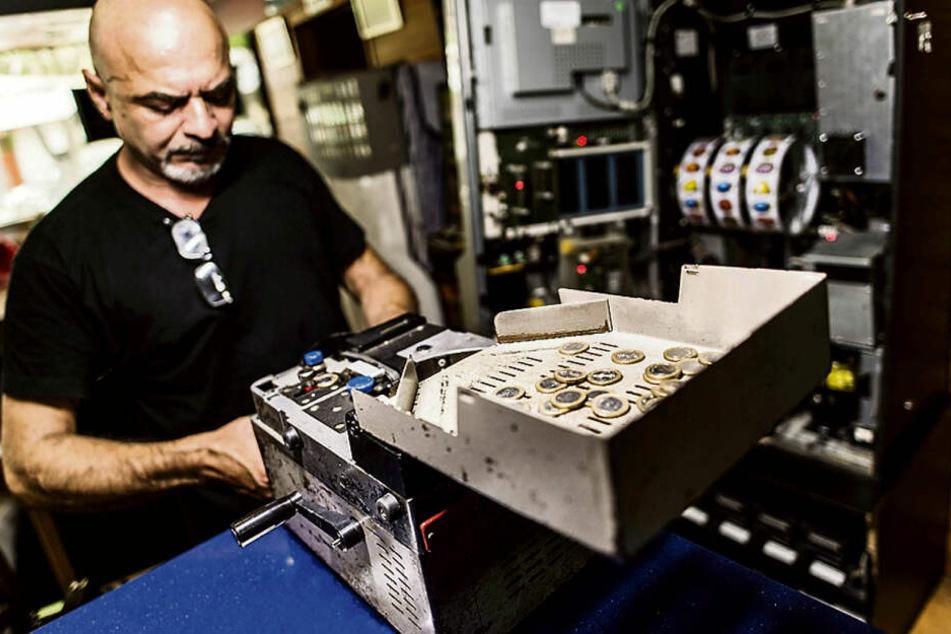 Ein Spielhallen-Mitarbeiter holt Geld aus einem Automaten. Um die Besteuerung tobt in Leipzig seit 13 Jahren ein Streit.