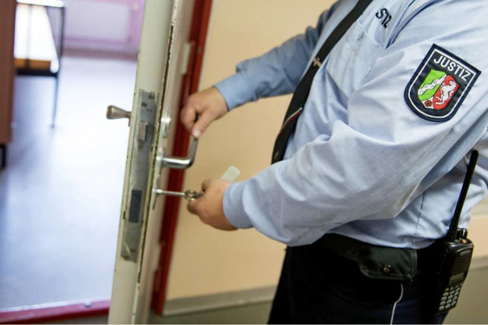 Ein Vollzugsbeamter der JVA Euskirchen schließt eine Zellentür auf.