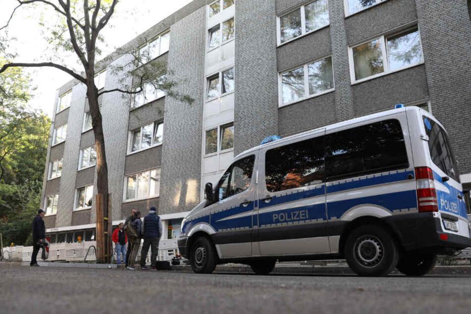 Ein Polizeiauto steht vor einem Haus in Hamburg, in dem eine Wohnung durchsucht wird.