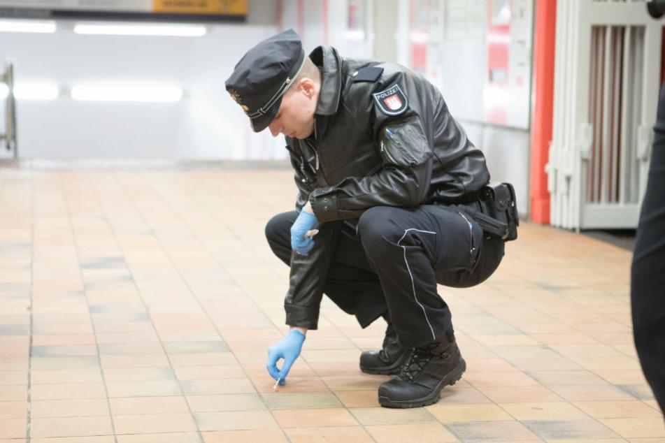 Ein Polizist sichert mit einem Wattestäbchen Spuren am Tatort.