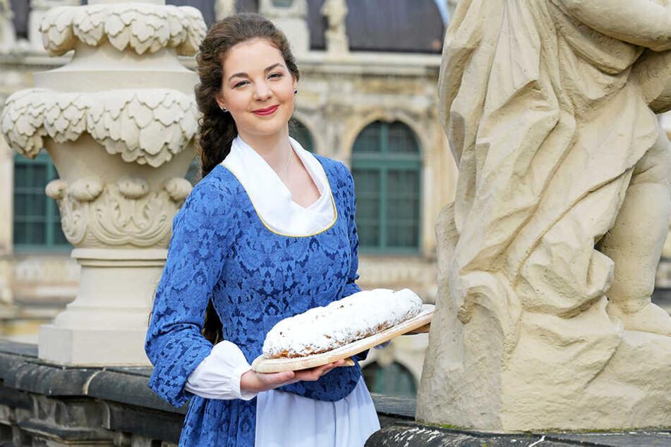 Mit Grazie und Leidenschaft präsentiert das Dresdner Stollenmädchen Veronika Weber (23) einen Stollen aus der Ottendorfer Mühlenbäckerei.