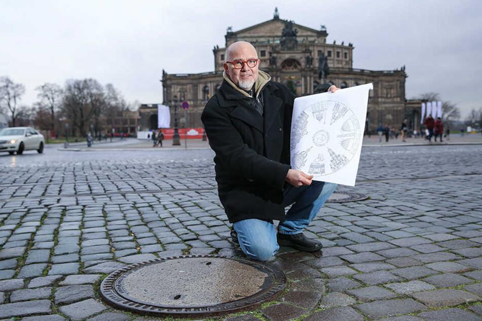 Künstler Peter Scharfe (56) zeigt einen der Deckel, der noch ausgetauscht wird. Die Semperoper im Hintergrund wird dann auf dem Gully verewigt.