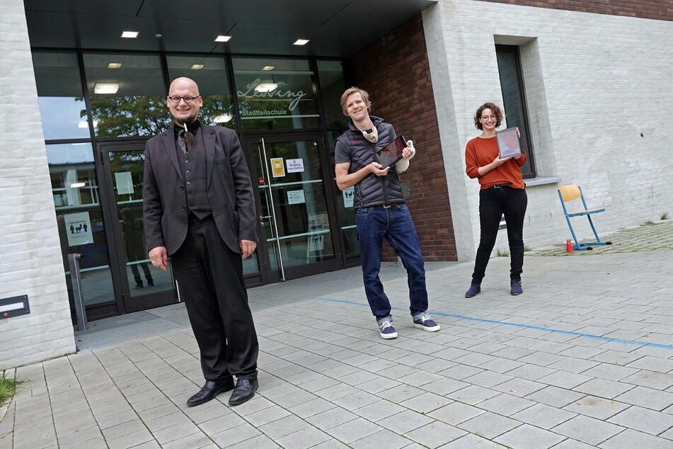 Schulleiter Tobias Stapelfeld (l.) sowie das Lehrerteam Hinrich Bühlker und Merle Heintz stehen vor dem Schuleingang der Lessing-Stadtteilschule in Hamburg-Harburg.