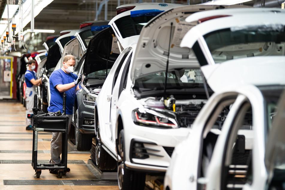 Ein Mitarbeiter setzt mit einem Mund- und Nasenschutz in der Produktion neben einem Auto.