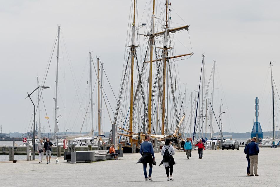 Besucher gehen am Hafen von Eckernförde entlang.