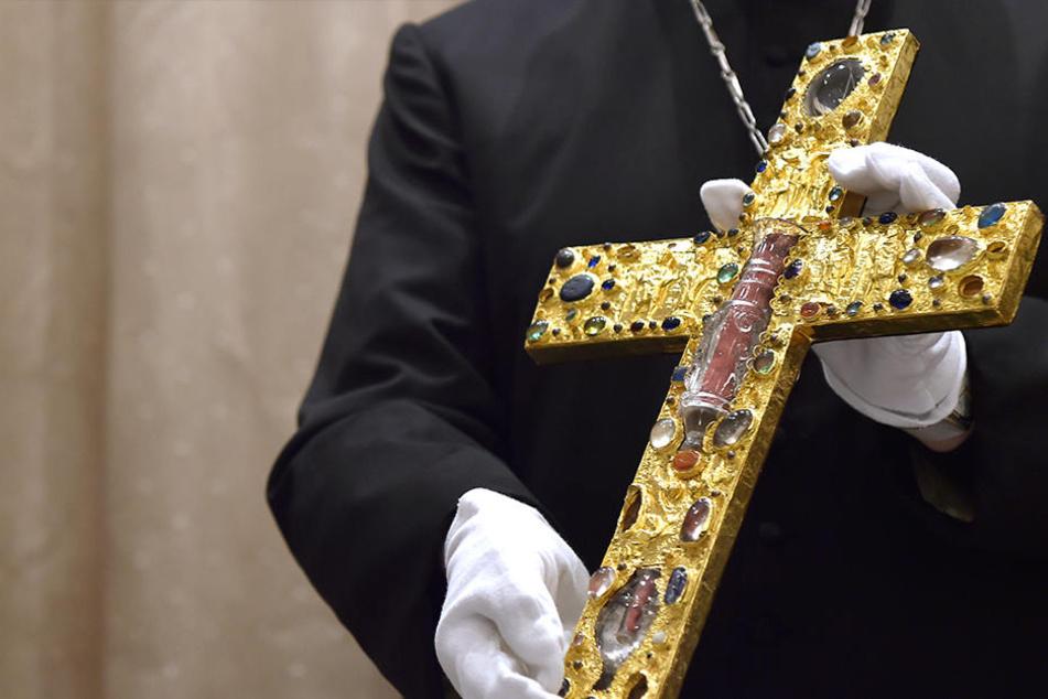 Das Kreuz ist mit Gold und Edelsteinen verziert.
