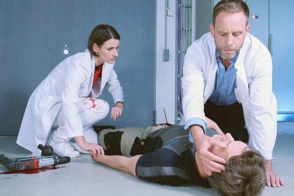 Hausmeister Henrik Weitzmann hat sich den Akkubohrer in die Leiste gerammt. Maria Weber und Kai Hoffmann eilen zu ihm.