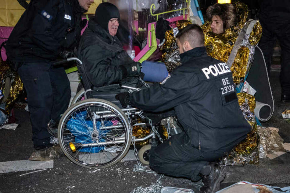 """Polizisten schneiden am Potsdamer Platz die Ketten eines Aktivisten der Klimabewegung """"Extinction Rebellion"""" mit einem Bolzenschneider durch."""
