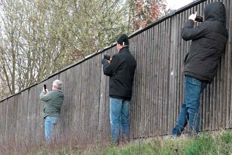 Schaulustige fotografieren neben einer Lärmschutzwand mit ihren Smartphones eine Unfallstelle.