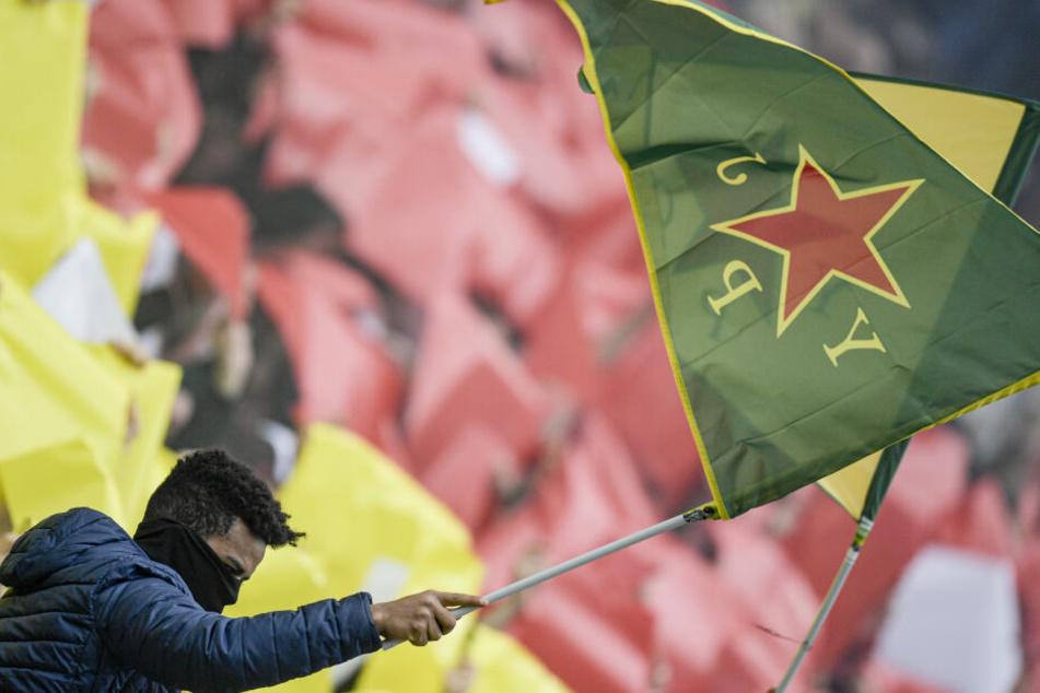 St. Paulis Fans halten Fahnen der kurdischen Frauenverteidigungseinheiten YPJ in die Höhe.