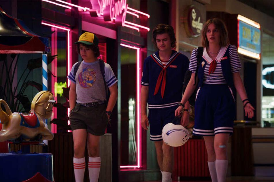 Dustin, Steve und Robin im klassischen Neon-Look der 80er.