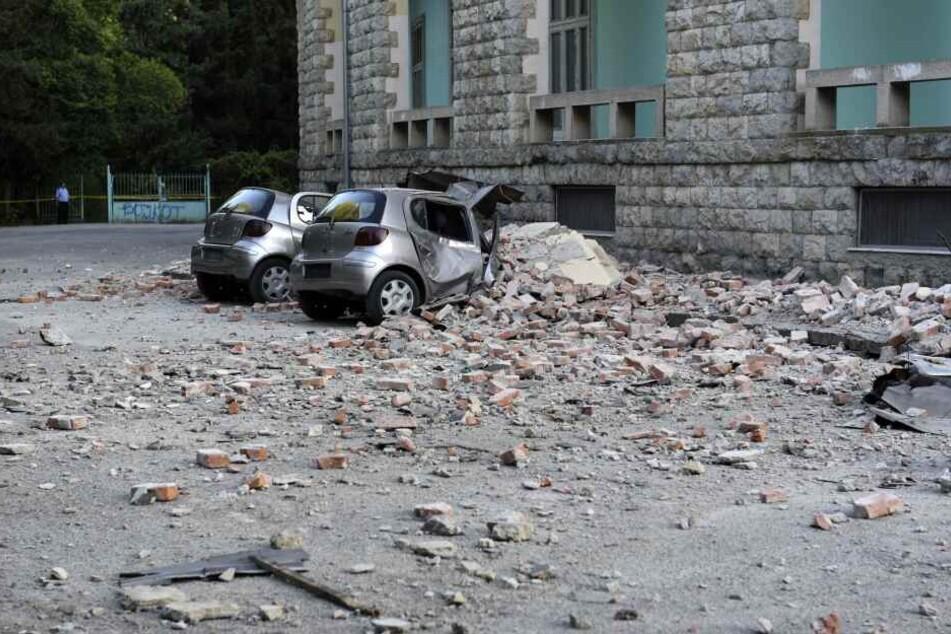 Zwei beschädigte Autos liegen nach einem Erdbeben unter den Trümmern vor dem Gebäude der Geologie-Fakultät.