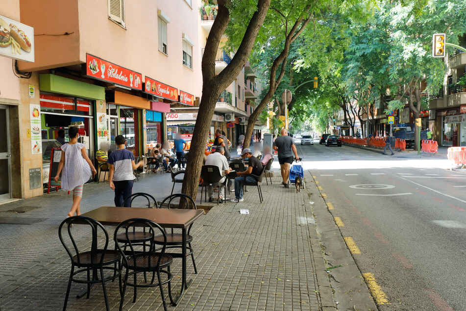 Nur wenige Menschen sitzen im Außenbereich eines Cafés im Stadtteil Son Gotleu auf Mallorca.