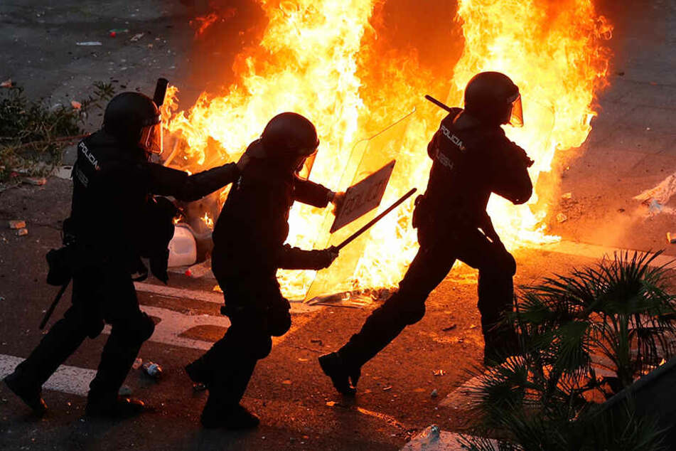 Polizisten laufen am Freitagabend an einer brennenden Straßenbarrikade in Barcelona vorbei.
