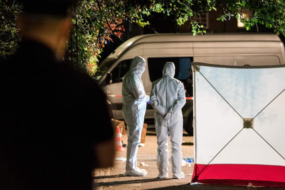 Polizisten in Schutzanzügen untersuchen im Stadtteil Lohbrügge den Tatort.