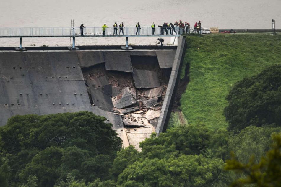 Menschen bilden über dem beschädigter Teil eines Staudamms am Toddbrook Reservoir eine Menschenkette um Sandsäcke auszulegen.