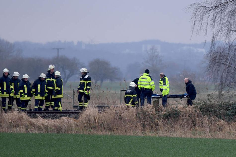 Feuerwehrmänner stehen an der Unglückstelle auf der Bahnstrecke Hamburg-Sylt nahe Wilster.