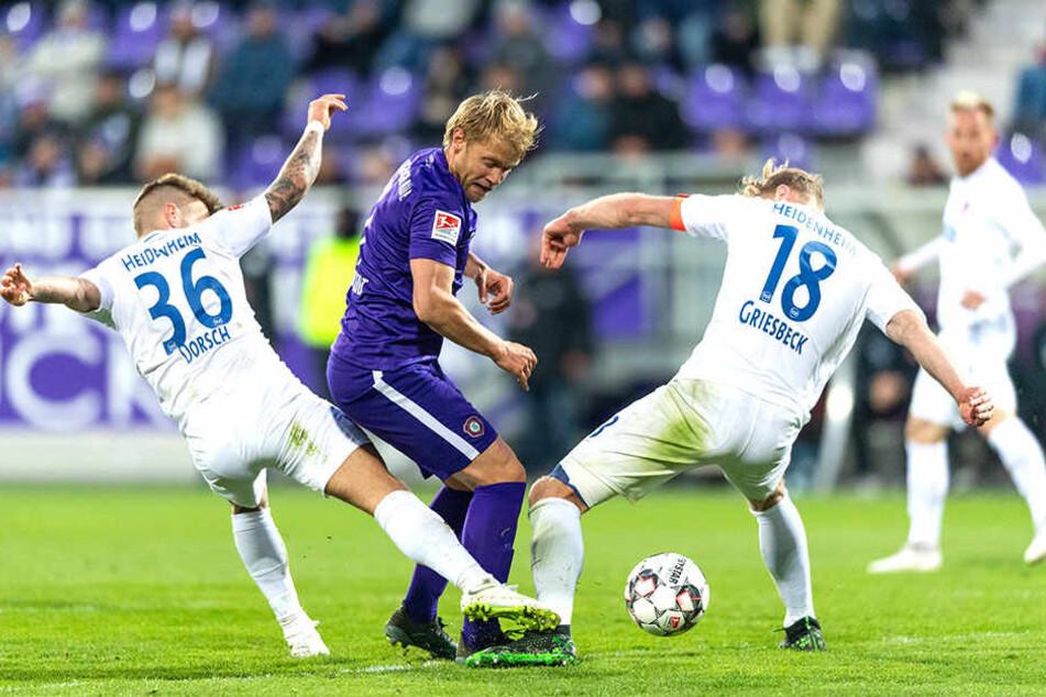 Ja, wer hat denn nun den Ball? Die Heidenheim Niklas Dorsch und Sebastian Griesbeck nehmen Aues Jan Hochscheidt in die Zange.