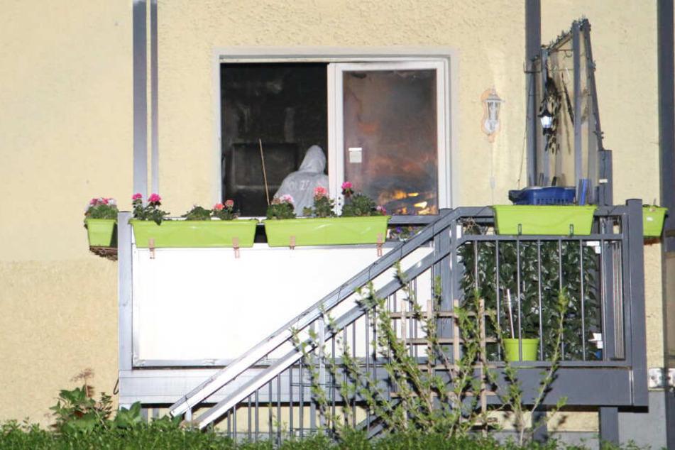 Ein Polizist steht im weißen Overall in der ausgebrannten Wohnung.