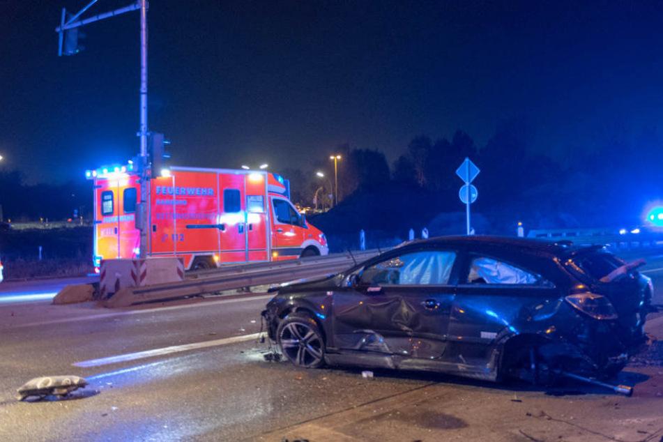 Das Auto ist nach dem Unfall schwer beschädigt, Teile liegen auf der Straße.
