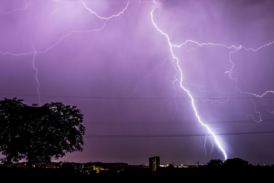 Blitze zucken während eines Gewitters am abendlichen Himmel über Stuttgart, Baden-Württemberg.