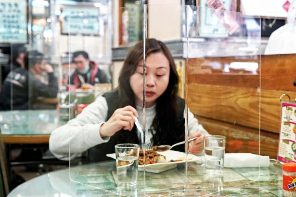 Eine Kundin sitzt hinter einer Plexiglaswand beim Mittagessen.