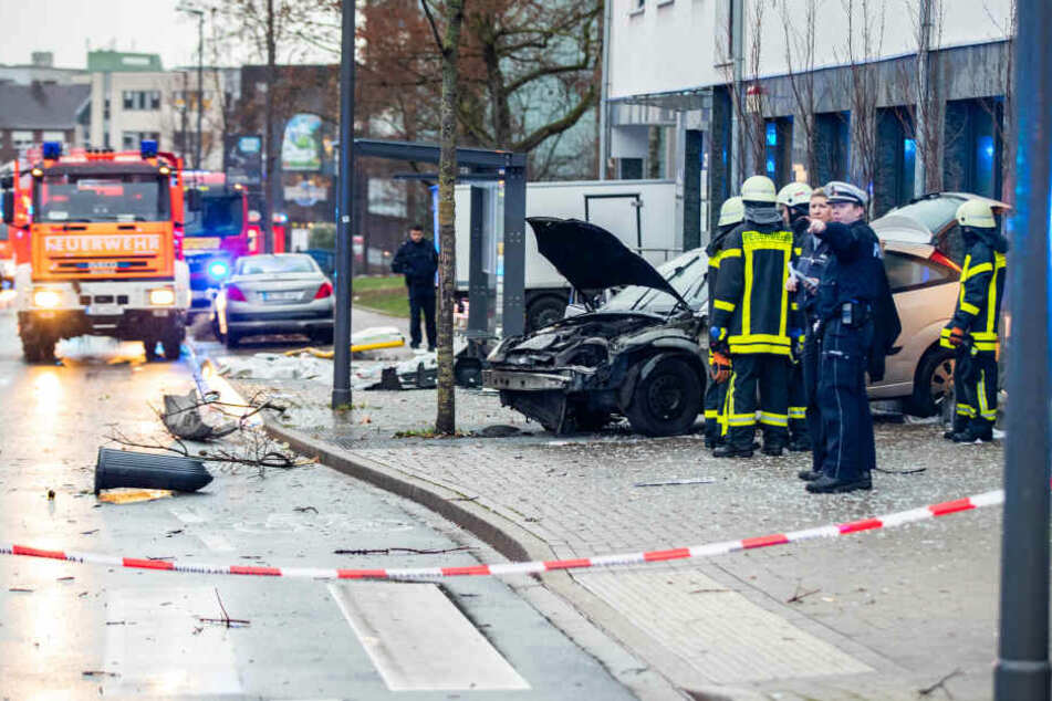 Polizisten und Feuerwehrleute stehenden neben dem beschädigten Auto an einer Bushaltestelle.