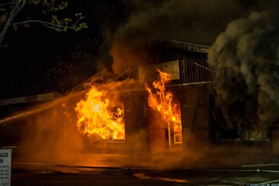 Flammen schlagen aus Fenstern und Türen des Gebäudes.