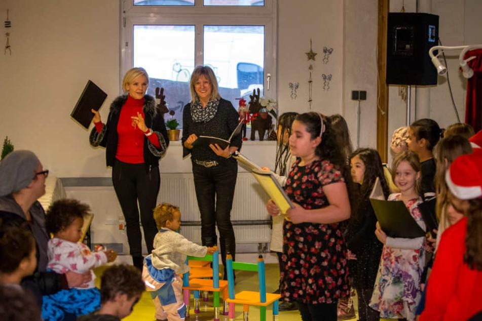 """Da kommt Stimmung auf: Die """"In aller Freundschaft""""-Schauspielerin Andrea Kathrin Loewig (52, l.) singt mit den Kindern der Leipziger Tafel Weihnachtslieder."""